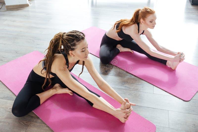 Twee vrouwen die zich op de vloer in yoga uitrekken centreren royalty-vrije stock fotografie