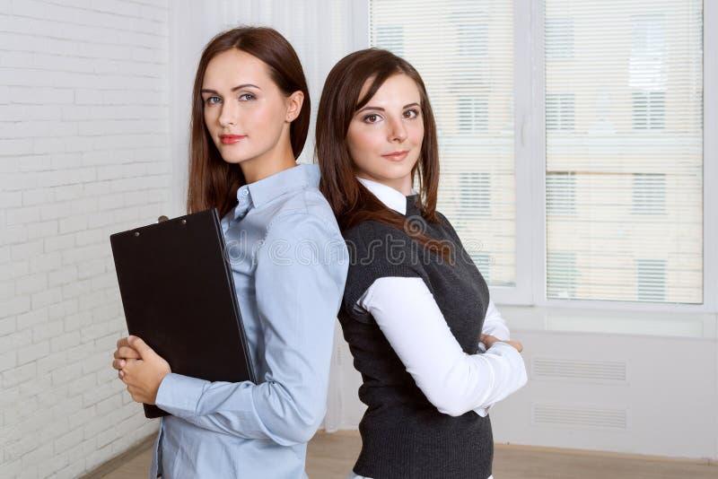 Twee vrouwen die zich rijtjes tegen het venster bevinden royalty-vrije stock afbeelding