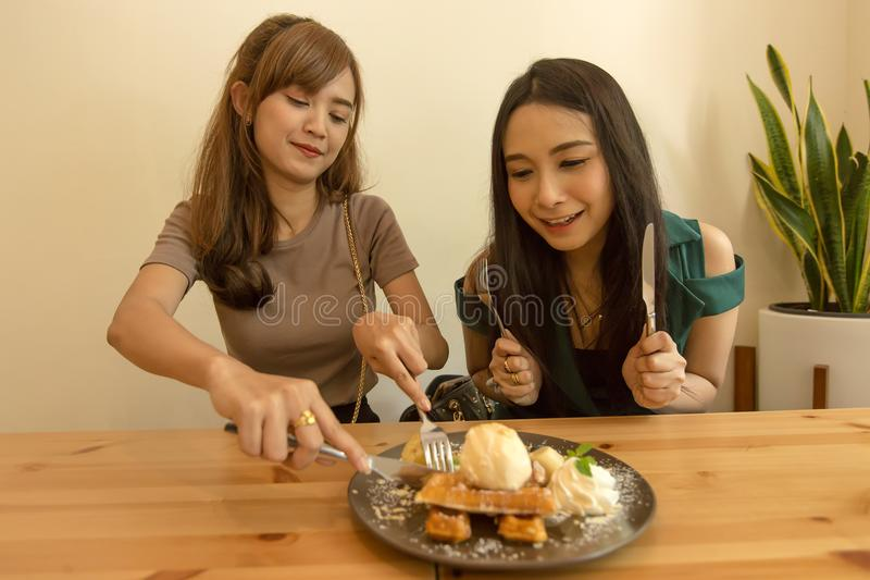 Twee vrouwen die zoet gezond dessert in een restaurant, het spreken en het besteden tijd samen verbruiken Het schone eten stock foto