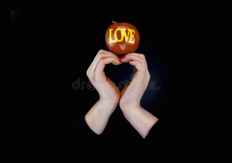 Twee vrouwen dient vorm van een hart en een appel met woordliefde in stock foto