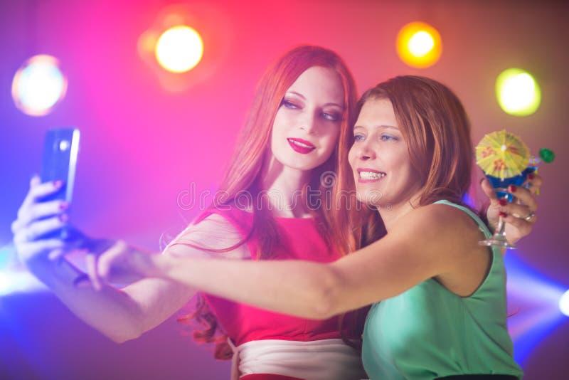Twee vrouwen in een nachtclub onder de schijnwerper met een binnen cocktail stock afbeeldingen