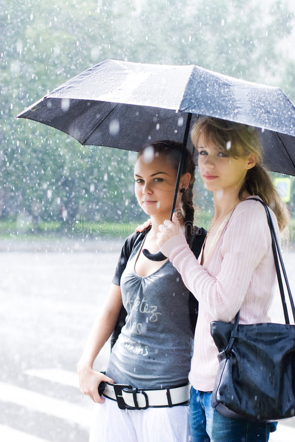 Twee vrouwen in een riany weer stock afbeeldingen