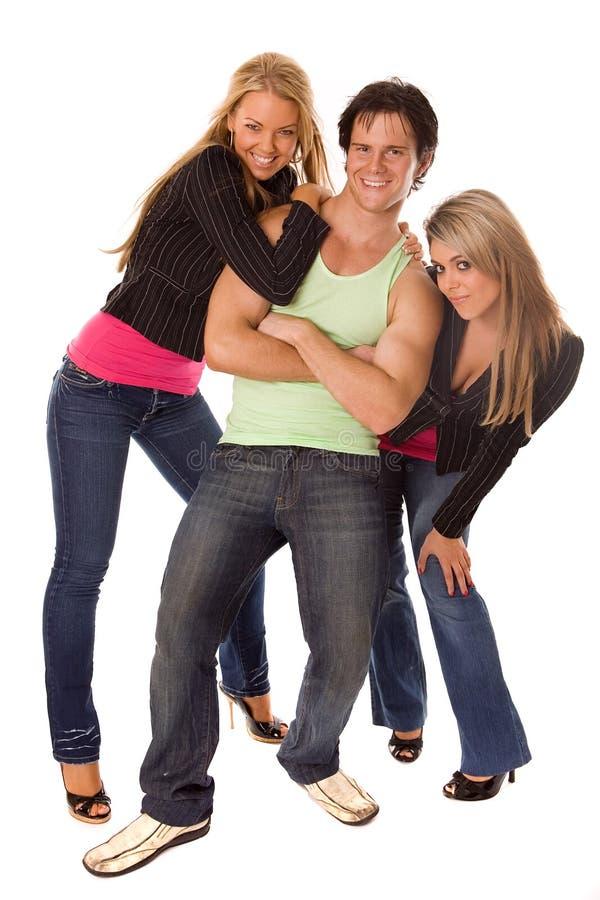 Twee vrouwen en man het stellen stock foto