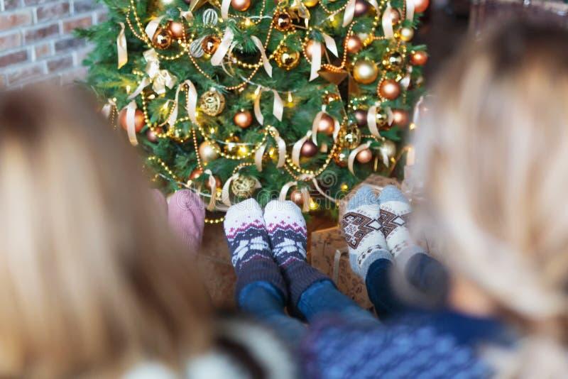 Twee vrouwen geklede Kerstmissokken die dichtbij Kerstboom zitten royalty-vrije stock fotografie