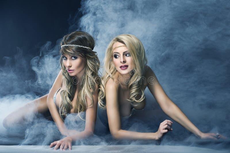 Twee vrouwen houden van sirene stock afbeeldingen