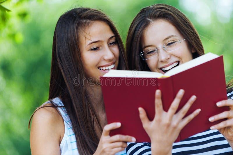 Twee vrouwen lezen rood boek royalty-vrije stock foto's