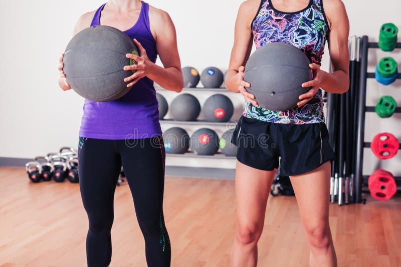 Twee vrouwen met geneeskundeballen stock afbeelding