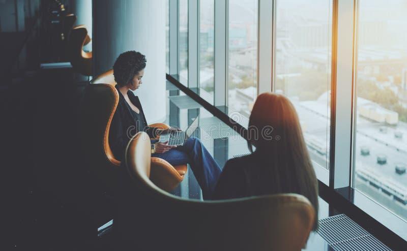 Twee vrouwen naast venster tijdens commerciële vergadering stock foto's