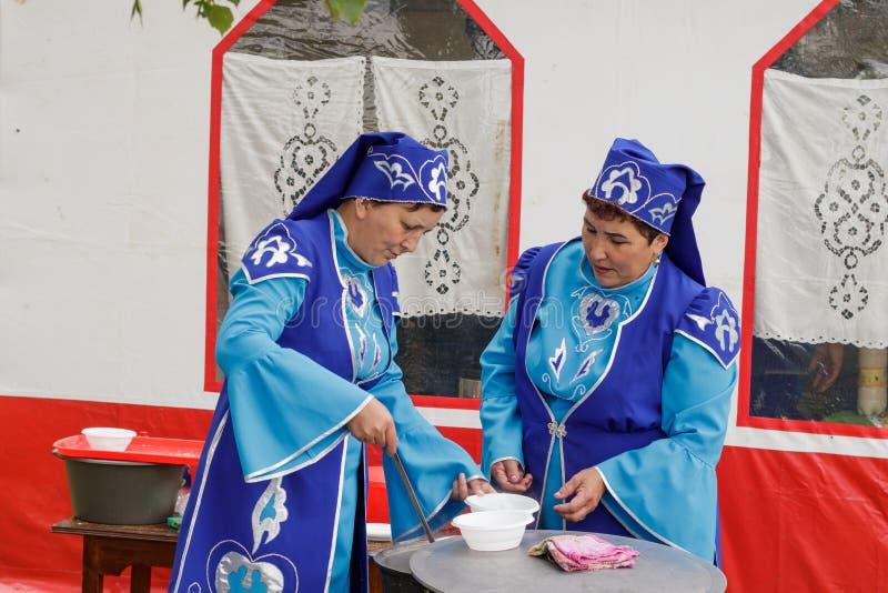 Twee vrouwen in nationale Tatar kleren giet soep in platen voor gasten van de vakantie Dag van het Siberische dorp van Nieuwe Yur royalty-vrije stock fotografie