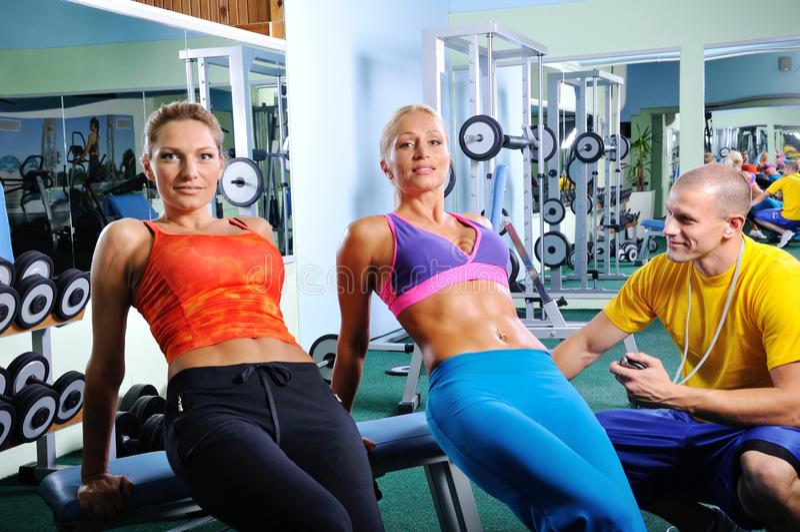 Twee vrouwen oefenen met persoonlijke geschiktheidstrainer uit royalty-vrije stock foto's