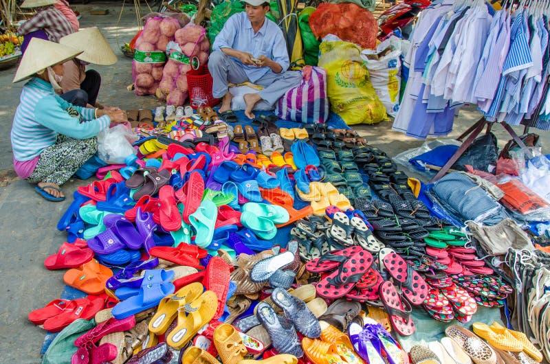 Twee vrouwen onderzoeken kleurrijke sandals en de schoenen voor verkoop bij een openluchtmarkt in Chan May, Vietnam stock fotografie