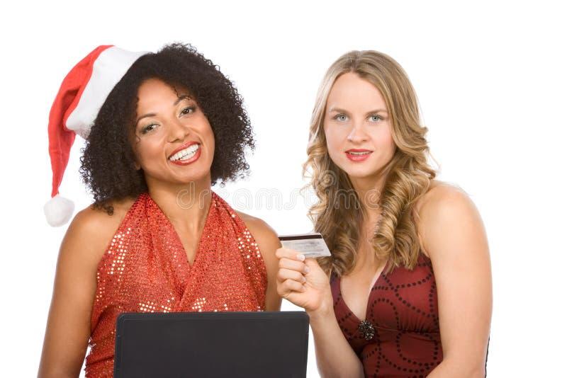 Twee vrouwen: Online het winkelen van Kerstmis gebruikende laptop stock afbeeldingen