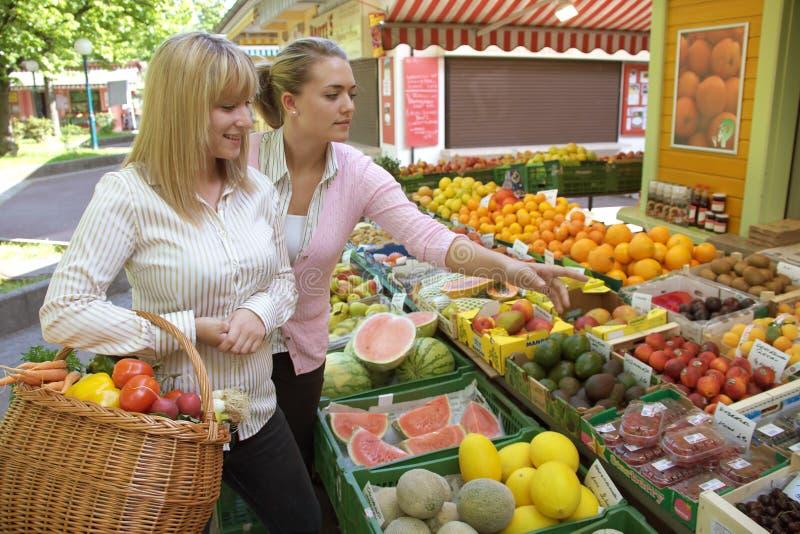 Twee vrouwen op de fruitmarkt stock afbeeldingen