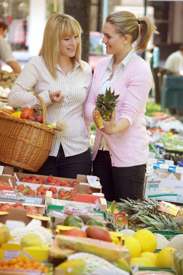 Twee vrouwen op de fruitmarkt stock fotografie