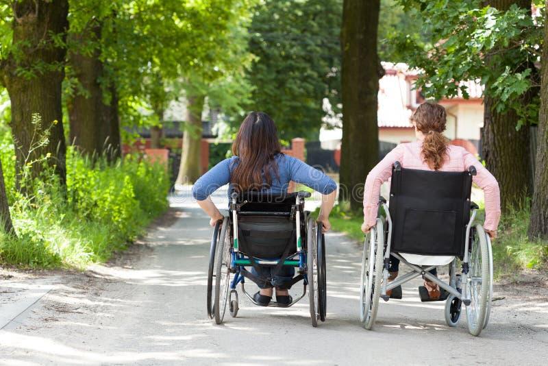 Twee vrouwen op rolstoelen in park stock foto's
