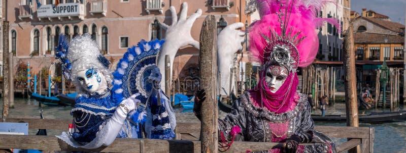 Twee vrouwen in roze en blauwe kostuums met ventilators en overladen geschilderde maskers voor het Sagredo-Hotel in Venetië Carni stock afbeeldingen