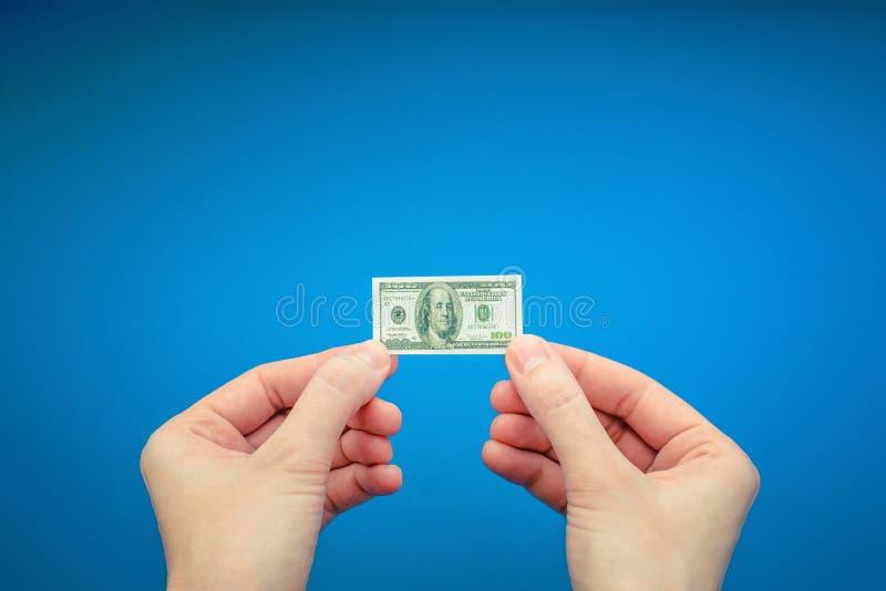 Twee vrouwen` s handen die klein bankbiljet van 100 Amerikaanse dollar houden stock afbeelding