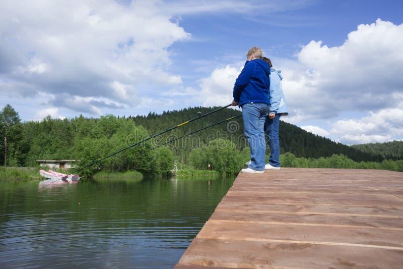 Twee vrouwen vangen vissen van het meer, die zich op een houten brug op de achtergrond van de beboste bergen van Kuznetsk bevinde stock foto's