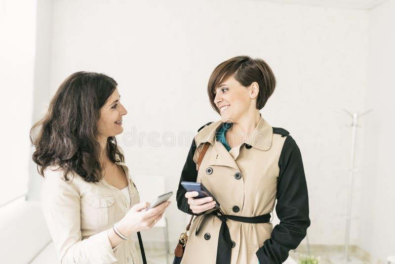 Twee vrouwen in wachtkamer glimlachen die haar telefoons kijken royalty-vrije stock fotografie