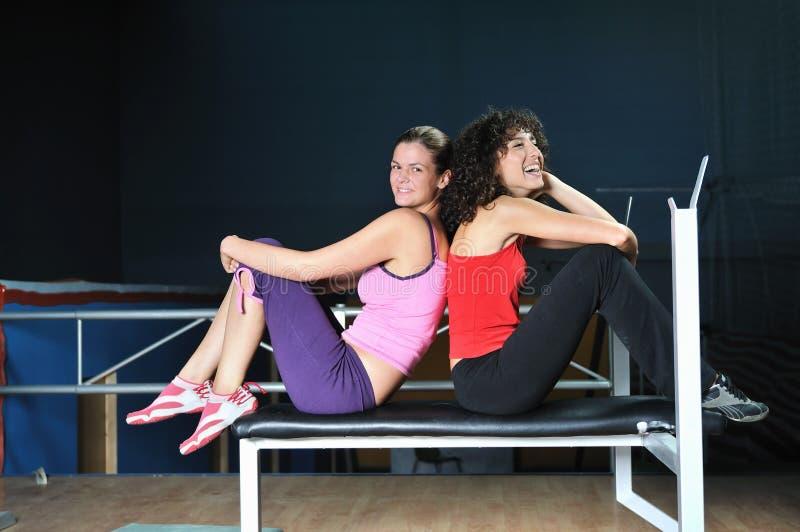 Twee vrouwen werken in geschiktheidsclub uit stock afbeelding
