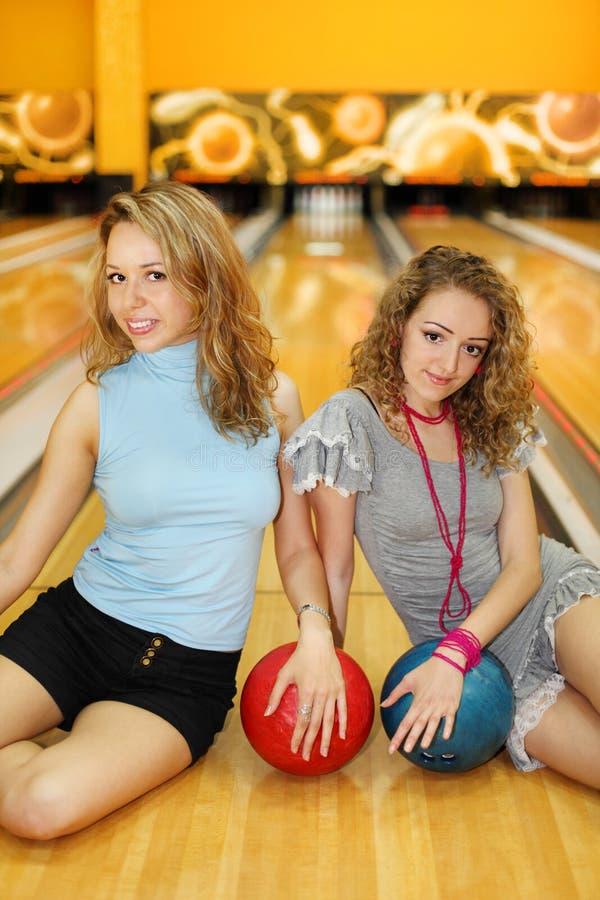 Twee vrouwen zitten op vloer met ballen in kegelenclub royalty-vrije stock afbeelding