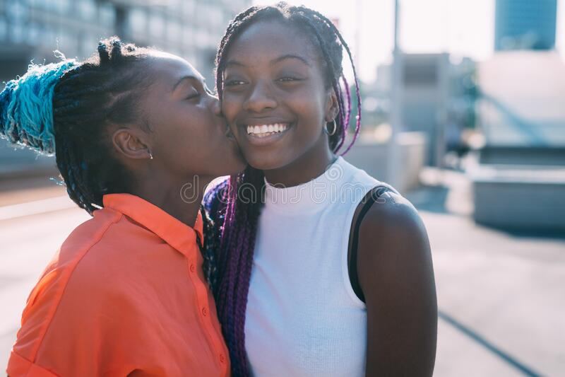 Twee vrouwen zussen in de buitenlucht die lachen en zoenen op de nek stock fotografie