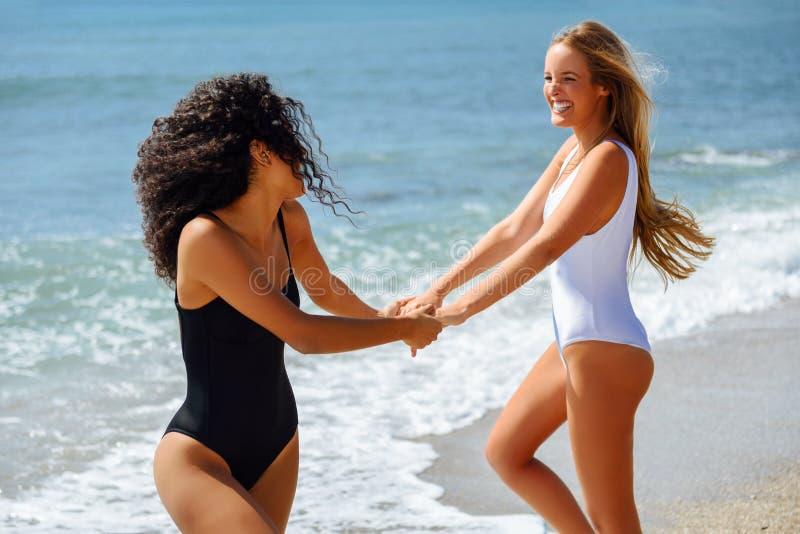 Twee vrouwen in zwempak die pret op het strand hebben stock foto's