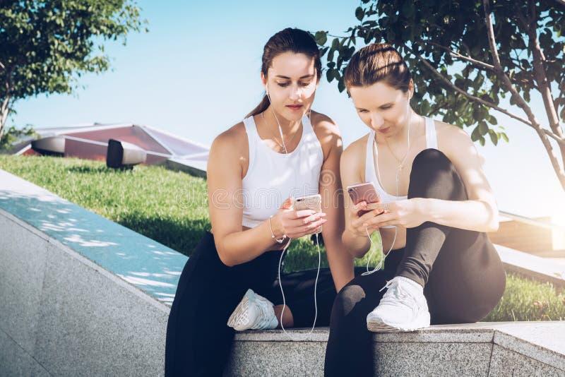 Twee vrouwenatleten in sportkledingszitting in park, ontspannen na sporten opleidend, gebruikssmartphone, luisterend aan muziek royalty-vrije stock afbeeldingen