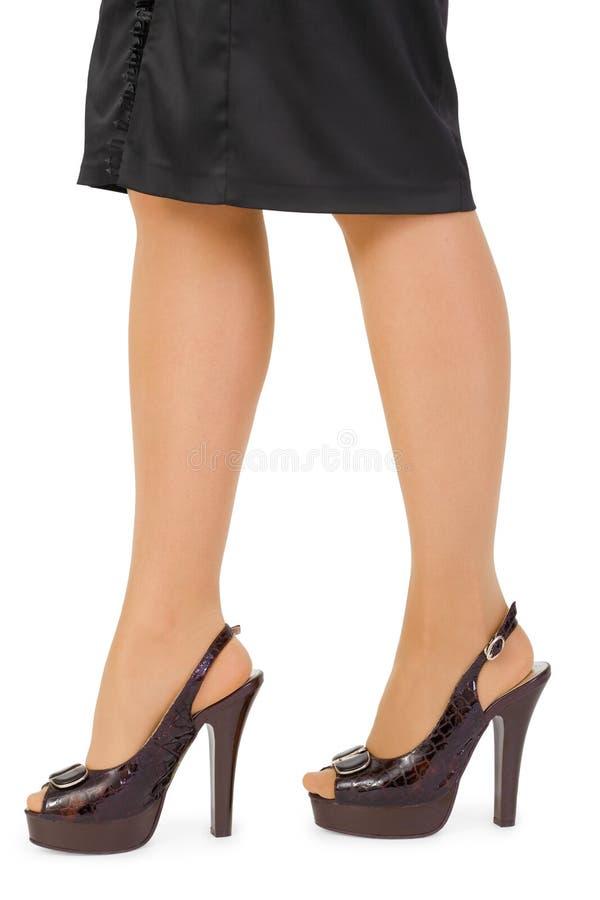 Twee vrouwenbenen in leerschoenen stock foto