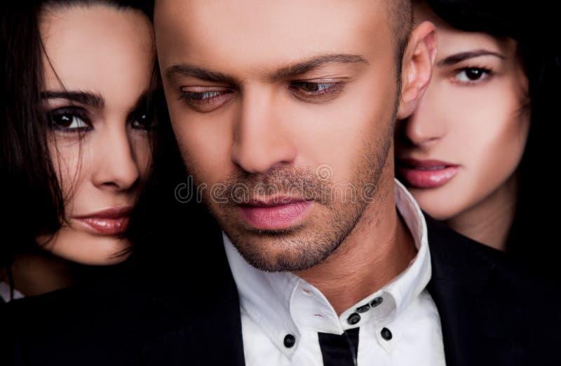 Twee vrouwengezichten achter mannetje