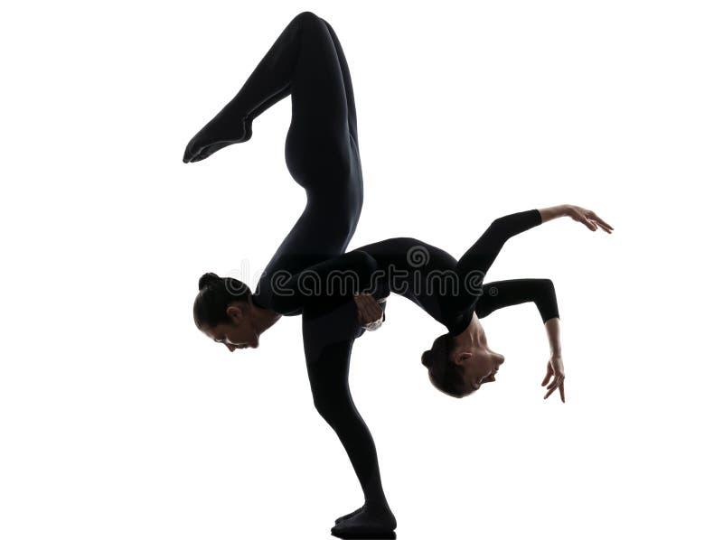 Twee vrouwenslangemens die gymnastiek- yogasilhouet uitoefenen stock foto's
