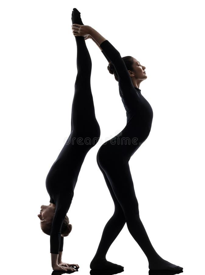 Twee vrouwenslangemens die gymnastiek- yogasilhouet uitoefenen stock afbeeldingen