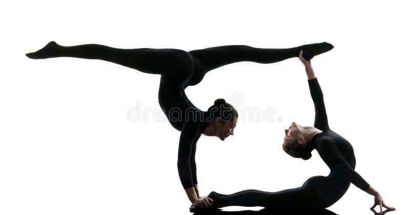 Twee vrouwenslangemens die gymnastiek- yogasilhouet uitoefent stock foto's