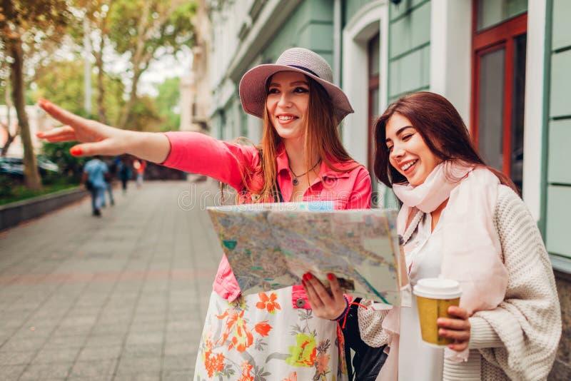Twee vrouwentoeristen die naar juiste manier zoeken die kaart in Odessa gebruiken Gelukkige vriendenreizigers die richting tonen stock afbeeldingen