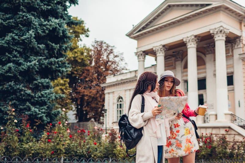 Twee vrouwentoeristen die naar juiste manier zoeken die kaart in Odessa gebruiken Gelukkige vriendenreizigers die richting tonen stock fotografie