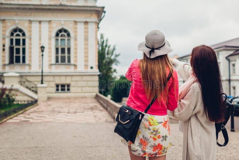 Twee vrouwentoeristen die naar juiste manier zoeken die kaart in Odessa gebruiken Gelukkige vriendenreizigers die richting tonen stock foto's