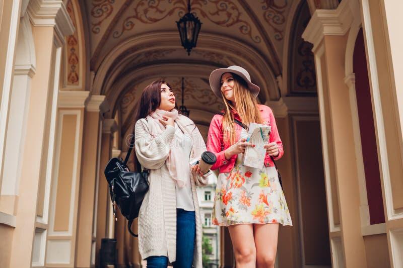 Twee vrouwentoeristen die terwijl gaand sightseeing in Odessa spreken Gelukkige vriendenreizigers gebruikend kaart en drinkend ko stock fotografie