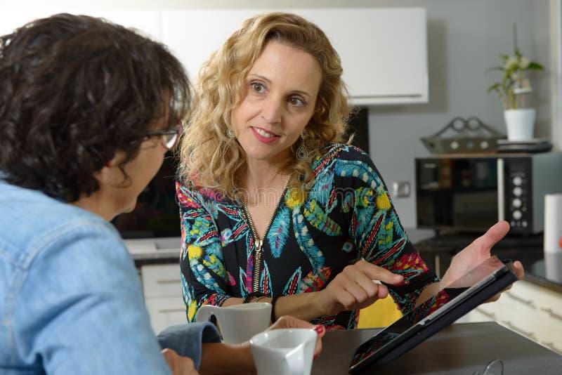 Twee vrouwenvrienden die digitale tablet bekijken stock fotografie