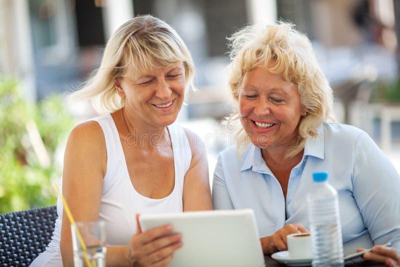 Twee vrouwenvrienden die tabletpc in openluchtkoffie met behulp van stock foto
