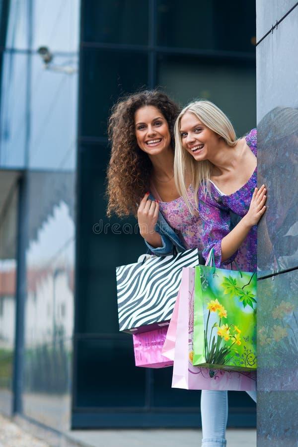 Twee vrouwenvrienden het winkelen stock afbeeldingen