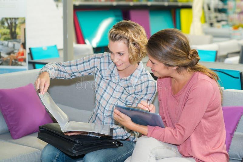 Twee vrouwenvrienden op de brochure van de banklezing royalty-vrije stock afbeelding