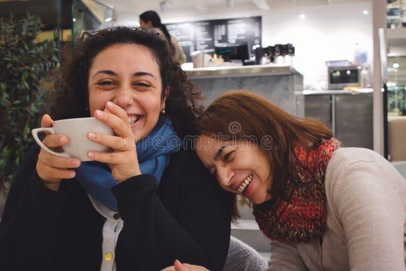 Twee vrouwenvrienden van een grap en van een praatje genieten en een kop die van koffie of thee, en in een koffie lachen glimlach royalty-vrije stock afbeeldingen