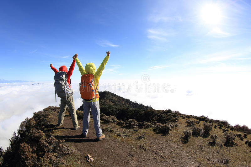 Twee wandelaars die aan zonsopgang op bergpiek toejuichen stock afbeelding