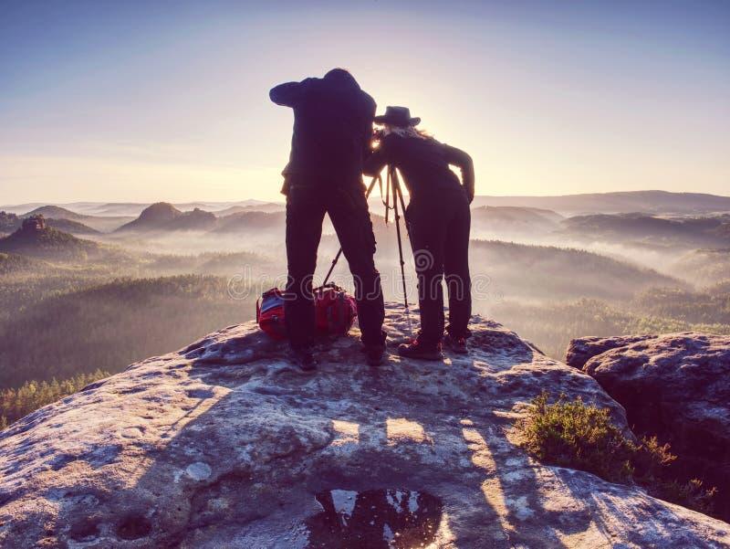 Twee wandelaars die beelden en bespreking bovenop berg nemen Twee fotografen royalty-vrije illustratie