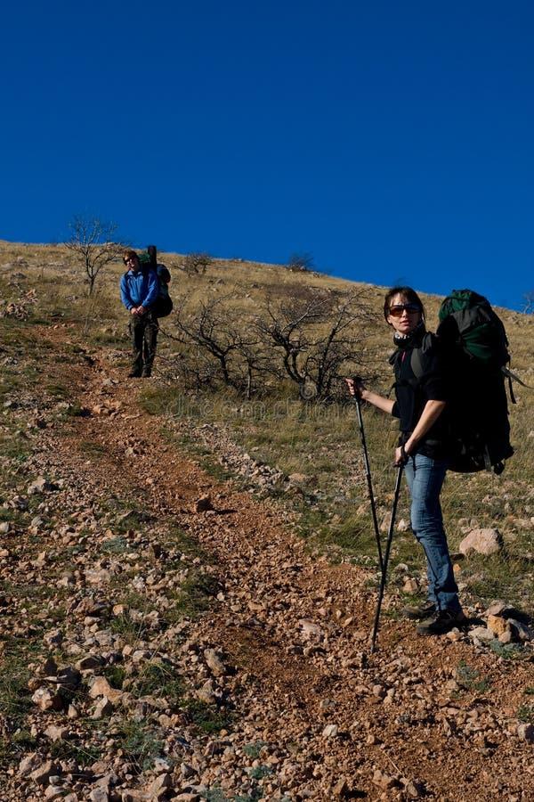 Twee wandelaars die op de berg beklimmen stock foto's