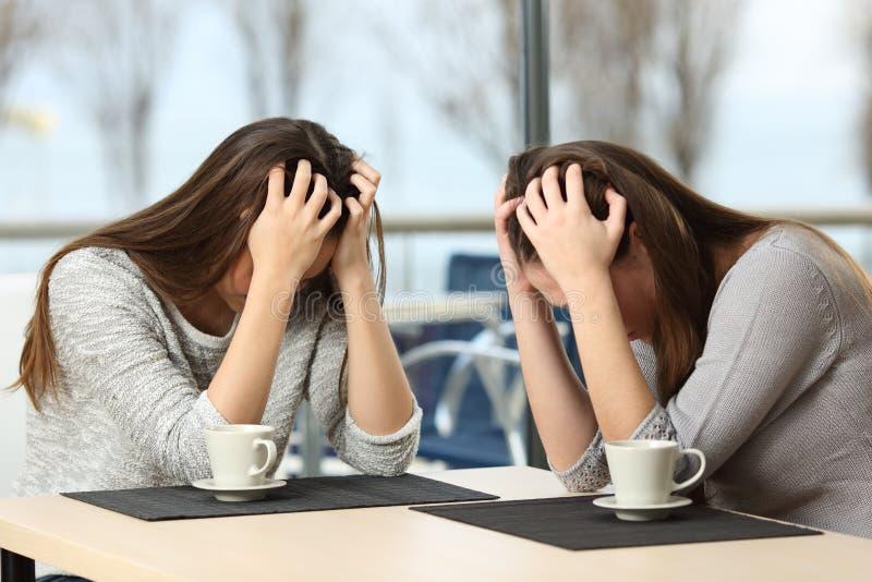 Twee wanhopige droevige meisjes in een bar stock foto's