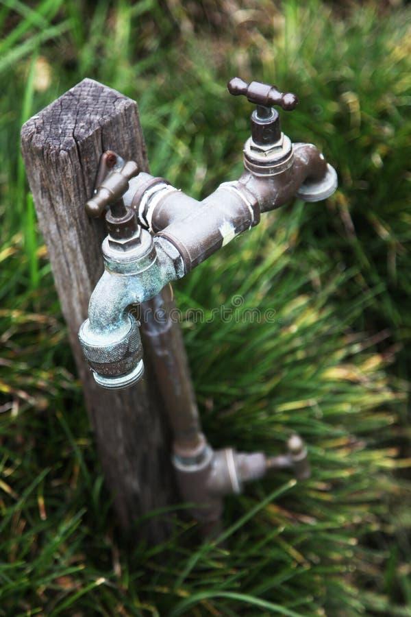 Twee waterkranen die één enkele pijp met behulp van royalty-vrije stock foto's