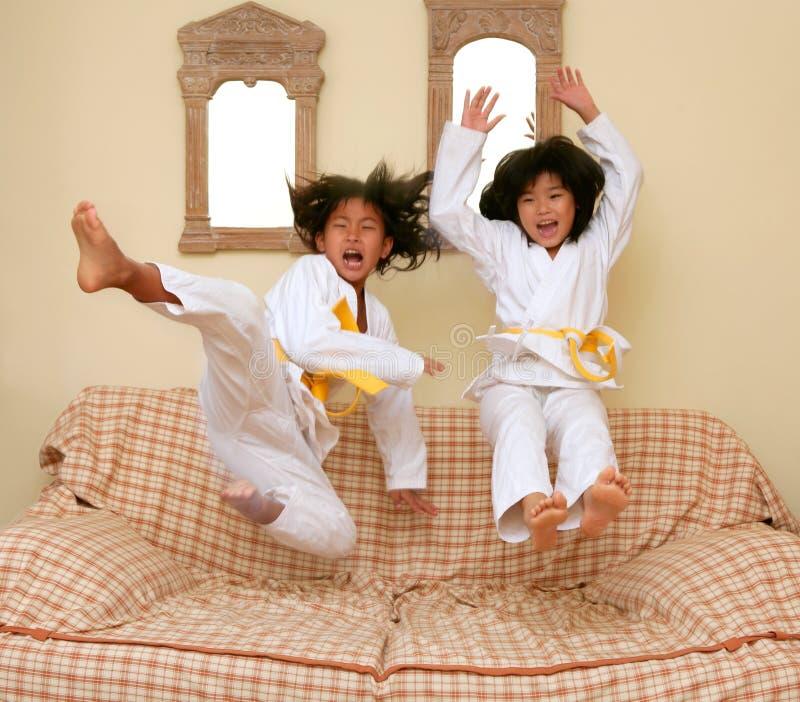 Twee weinig Aziatisch judo gils springen op bank royalty-vrije stock fotografie