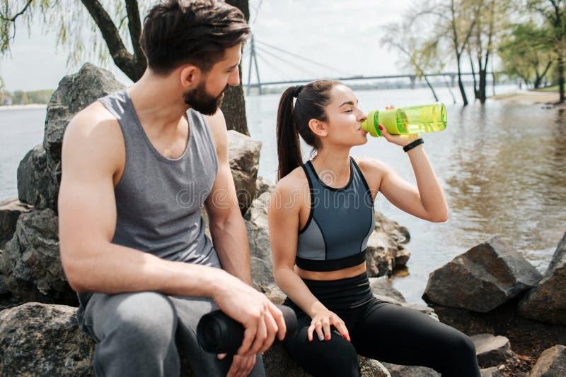 Twee well-built mensen hebben wat rust zij bij de rivierkust zitten Het meisje is drinkwater van de fles stock afbeelding