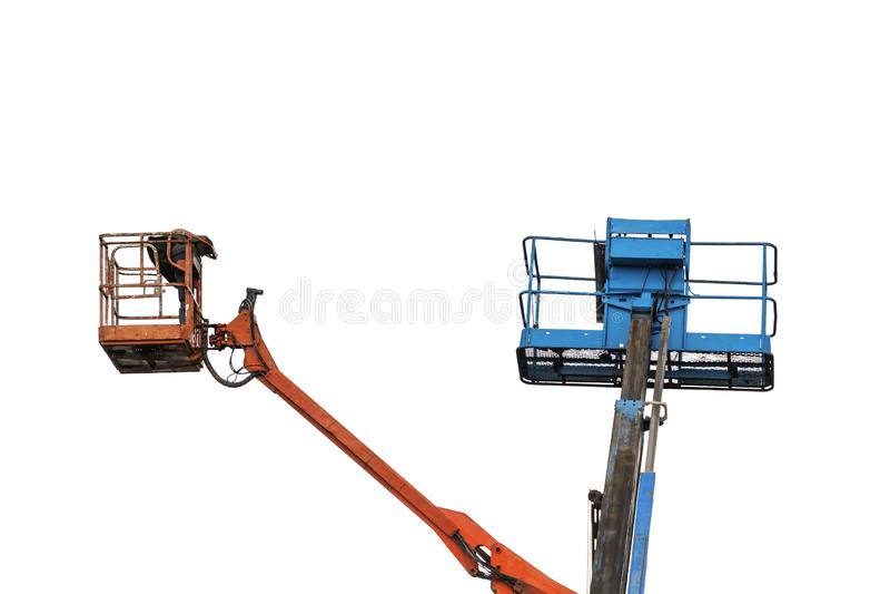Twee werkende hydraulische luchtplatforms voor het werk op grote hoogte in rood en geïsoleerd blauw stock afbeelding